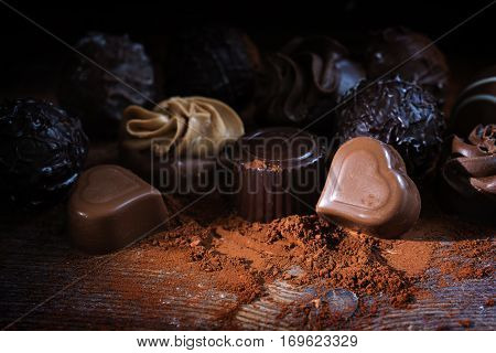 Chocolate pralines and cocoa powder on rustic wood as a love gift close up against a dark background selected focus narrow depth of field