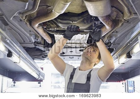 Mid adult automobile mechanic repairing car in workshop