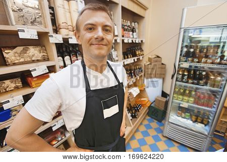 Portrait of confident mid adult salesman standing hands on hips in grocery store