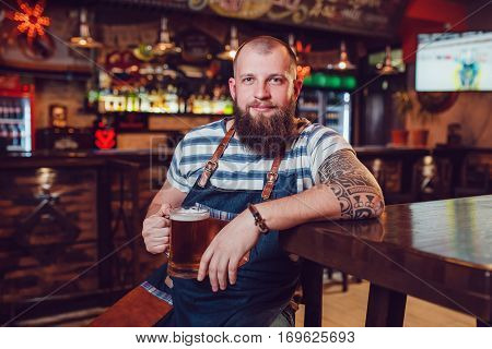 Bearded barman with tattoos wearing an apron sitting in bar and holding a glass of beer