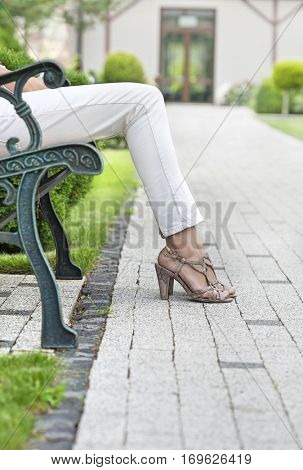 Low section of young woman relaxing on park bench