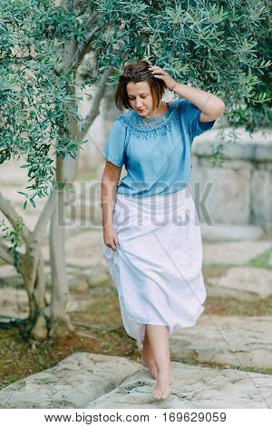 in the Park under a tree posing a woman in a white skirt and blue jacket