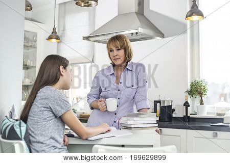 Mother having coffee while looking at daughter studying in kitchen