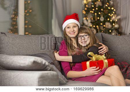 Happy girl hugging sister on sofa during Christmas