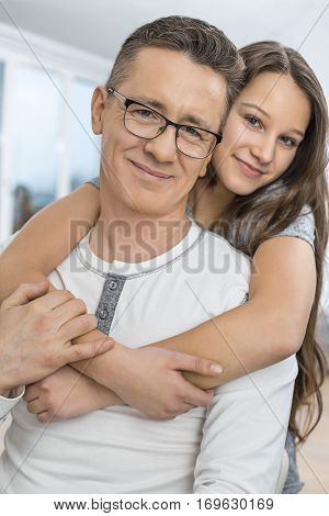 Portrait of affectionate girl embracing father from behind at home