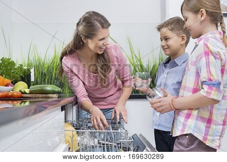 Happy mother and children placing glasses in dishwasher