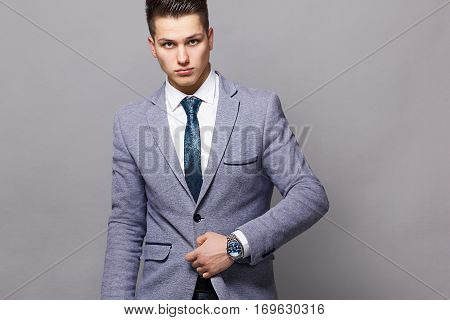 Elegant young handsome man wearing glasses and watchers. Studio fashion portrait.