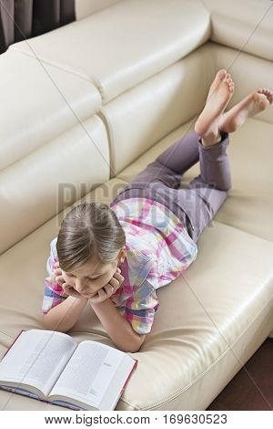 High angle view of girl reading book while lying on sofa at home