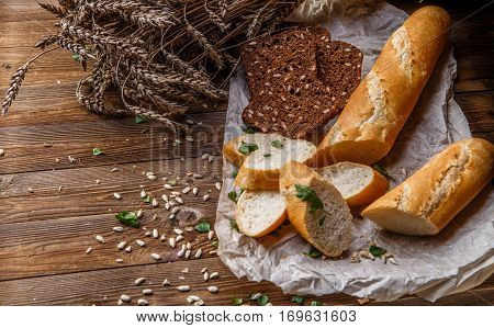Different bread lying on wax paper at wooden table