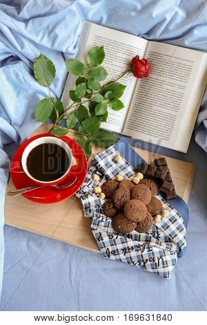 Breakfast served in bed - cup of coffee, chocolate cookies, chocolate, hazelnuts on a wooden board on background of light blue bed linens, open book and red rose. Festive breakfast in bed concept.