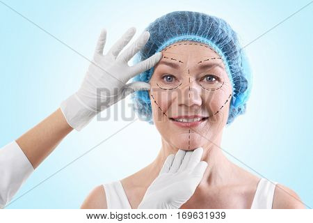 Surgeon examining female face against blue background. Plastic surgery concept