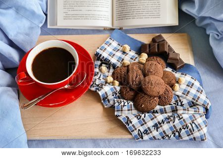 Breakfast served in bed - cup of coffee, chocolate cookies, chocolate, hazelnuts on a wooden board on background of light blue bed linens, open book. Festive breakfast in bed concept.