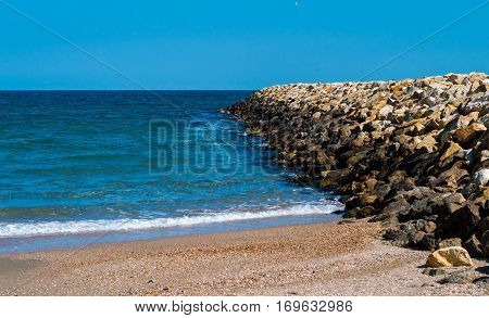 View from the shore into the bright blue sea and the breakwater on the right.