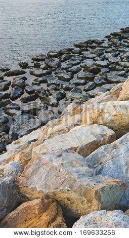 Dark and light stones in the breakwater in water.