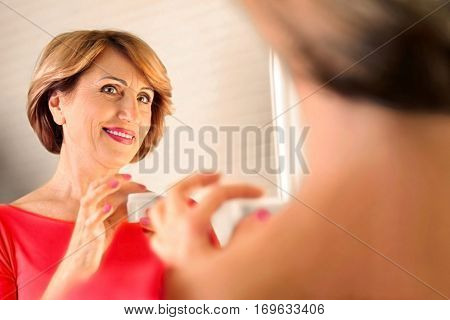 Senior woman looking in mirror while applying anti-aging cream onto face