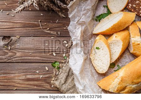Warm bread in wooden bowl on table with wheat and linen cloth