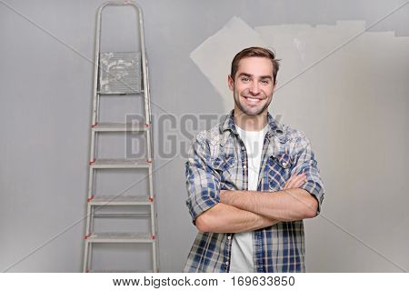 Handsome young decorator in room prepared for repair