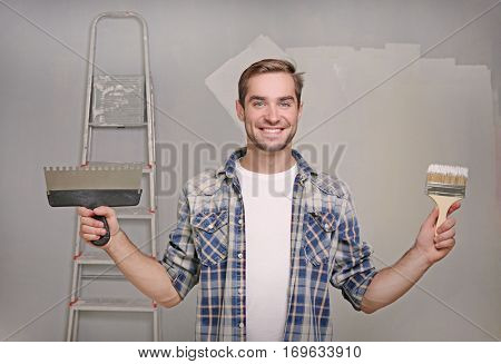 Handsome young decorator with putty knife and brush in room prepared for repair