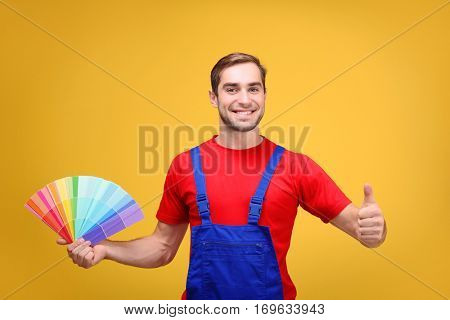 Handsome young decorator with color samples on yellow background