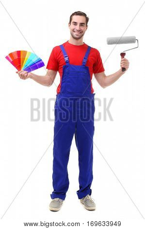 Young decorator holding color samples and paint roller, on white background