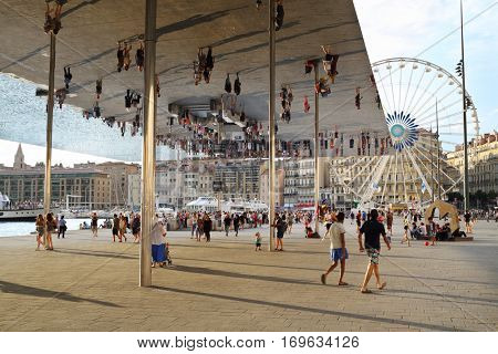 MARSEILLE, FRANCE - JUL 31, 2016: People walk under reflecting awning made of polished steel by British architect Lord Norman Foster at Old port of Marseille