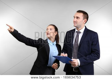 Young man and woman discussing something on light background
