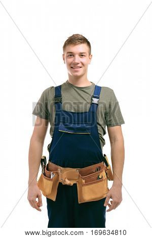 Handsome young man with tools belt on white background