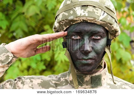 Close up view of saluting soldier on blurred green background
