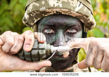 Close up view of soldier pulling safety pin out of fragmentation grenade, on blurred green background