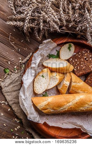 Baguette, fresh bread in bowl on wooden table