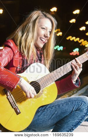 Youth Street Life Concepts. Portrait of Smiling Caucasian Blond Girl Playing the Guitar Outside on Street. Combination of Flash and Halogen. Vertical Image