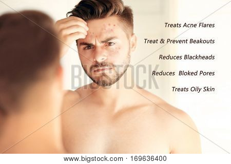 Skin care concept. Young man looking into mirror