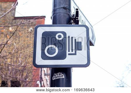 Closeup on speed camera street sign in a post. white sky on the background