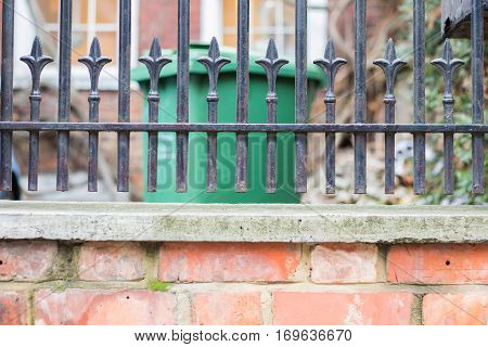 The bottom part of metal fence over a brick wall