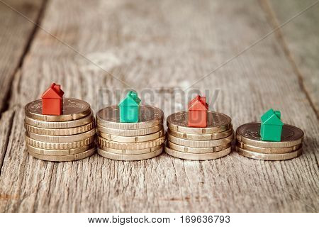 Miniature plastic houses on top of stacked coins