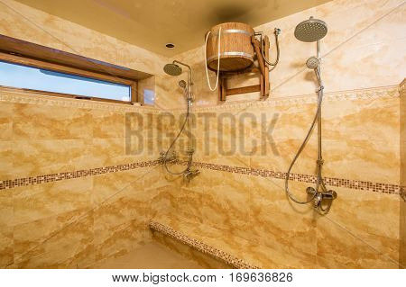 spacious interior of empty bathroom with marble tiles. A cold shower after a hot steam