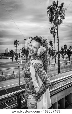 Smiling Trendy Tourist Woman In Earmuffs In Barcelona, Spain