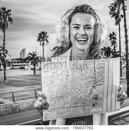 in Barcelona for a perfect winter. smiling modern woman in earmuffs on embankment in Barcelona Spain with map