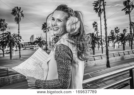 in Barcelona for a perfect winter. smiling modern traveller woman in earmuffs on embankment in Barcelona Spain with map looking into the distance