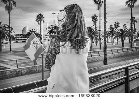 Modern Woman In Earmuffs In Barcelona With Spanish Flag