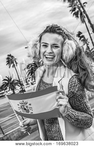 Smiling Young Traveller Woman In Barcelona, Spain Showing Flag