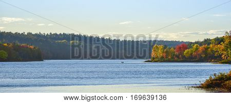 Two people floating in a small in the distance on the surface of a lake in summer late afternoon sun.  Late summer colors emboldened by late afternoon, golden sunlight.