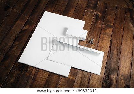 Blank letterhead business cards and envelope. Photo of blank stationery on wooden table background. Mockup for branding identity. ID template.