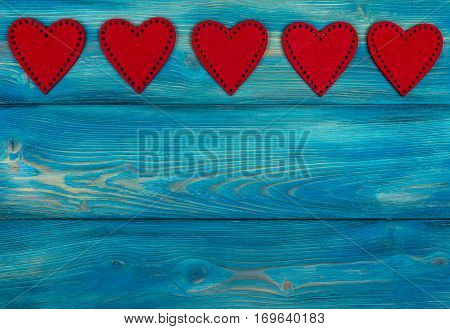 red hearts on the blue rustic wooden background with woodgrain texture
