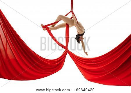 Young girl in beige body streching gracefully on red aerial silks in studio