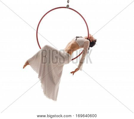 Young girl in white lace skirt and top sitting on a hoop and streching gracefully in studio
