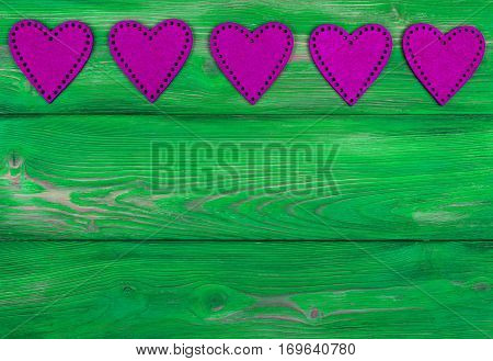 pink hearts on the green rustic wooden background with woodgrain texture