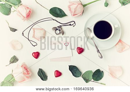 Romantic love still life - cup of coffee peach roses blank card owl shaped clock heart shaped candies on white background. Flat lay top view of love romantic backgorund. Love romantic concept