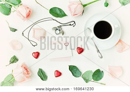 Love romantic background - cup of coffee peach roses blank card for love message owl shaped clock heart shaped candies on white background. Flat lay top view. Love romantic still life, romantic love concept