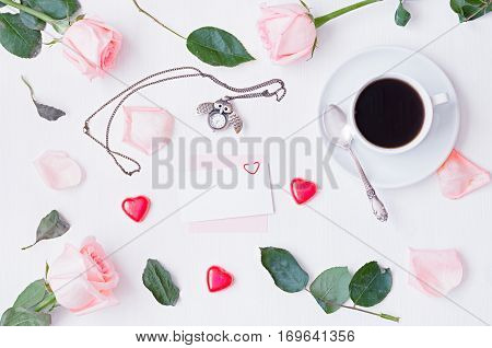 Love romantic St Valentines day background - cup of coffee, peach roses, blank card for love romantic message, owl shaped clock, heart shaped candies on white background. Flat lay top view of romantic love still life